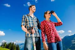 Koppla ihop att tycka om sikten som fotvandrar i de alpina bergen Arkivbilder