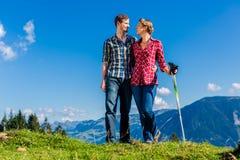 Koppla ihop att tycka om sikten som fotvandrar i de alpina bergen Royaltyfria Foton