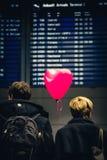 Koppla ihop att vänta på något på ankomstområdet av MUC-flygplatsen arkivfoto