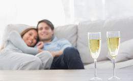 Koppla ihop att vila på en soffa med flöjter av champagne arkivbild