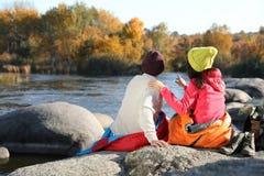 Koppla ihop av campare i sovsäckar som sitter på, vaggar nära dammet royaltyfri foto