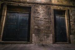 Koppla ihop av dörrar i en mörk gata royaltyfri foto