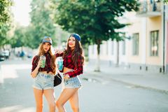 Koppla ihop av flickvänner som poserar på gatan och dricker coctailar fotografering för bildbyråer