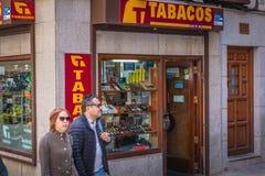 Koppla ihop av forties som passerar en tobak shoppar i Toledo arkivbild