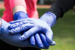 Koppla ihop av händer i de medicinska handskarna för latexet royaltyfria foton