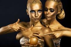 Maskerad. Njutning. Två glansiga kvinnor med guld- förkroppsligar konst. Glamour Royaltyfria Bilder