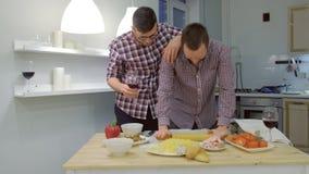 Koppla ihop av män som bögen rullar ut pizzadegen, och laga mat tillsammans att krama och att dricka ett vin lager videofilmer