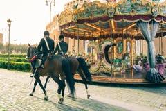 Koppla ihop av polisen på hästrygg som förbigår en karusell i staden av Rome Varma, mjuka och orange färger royaltyfri bild