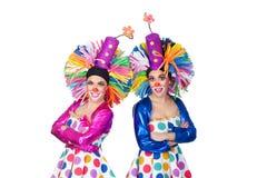 Koppla ihop av roliga clowner med stora färgrika wigs royaltyfria bilder
