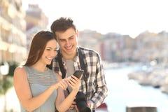 Koppla ihop av turister som kontrollerar det smarta telefoninnehållet på semester arkivbilder