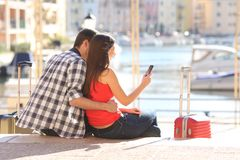 Koppla ihop av turister som kontrollerar mobiltelefonen på semester arkivbilder