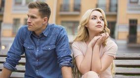 Koppla ihop avbrott upp, den upprivna mannen och skriande kvinnasammanträde på bänk, skilsmässa arkivfoton