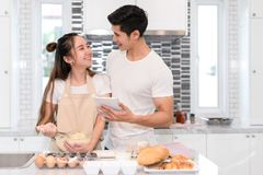 Koppla ihop danandebagerit, kakan i kökrum, den unga asiatiska mannen och kvinnan royaltyfri foto