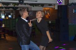 Koppla ihop dansen i en stång passionerad dans Deltagare i klubban Grabben drar flickan vid pärlorna royaltyfri fotografi