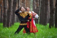 Koppla ihop dansen i traditionell klänning för ryss på naturen royaltyfri bild