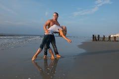 Koppla ihop dansen på stranden Arkivfoto