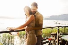 Koppla ihop den förälskade skämtandet i en terrass på sjön royaltyfri bild