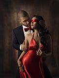 Koppla ihop den förälskade sexiga modekvinnan och mannen, flicka med den röda musikbandet på ögon som charmar pojkvännen i dräkte Arkivfoto