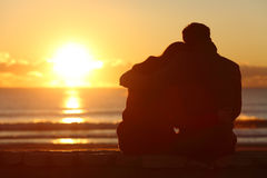 Koppla ihop den hållande ögonen på solnedgången på stranden i vinter Arkivbilder