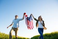 Koppla ihop den hållande amrican flaggan och spring i fält royaltyfria bilder