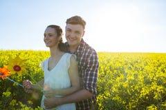 Koppla ihop den hållande lilla solen och att omfamna sig i senapsgult fält royaltyfri fotografi