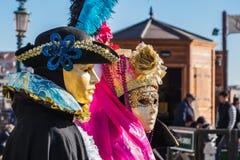 Koppla ihop den iklädda svart- och rosa färgdräkten på den Venedig karnevalet Arkivbild