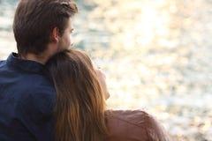 Koppla ihop den krama och hållande ögonen på solnedgången på stranden Royaltyfria Bilder