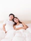 Koppla ihop det lyckliga leendet som ser för att tömma kopieringsutrymme i säng Royaltyfria Foton