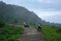 Koppla ihop ett varit nedstämd lopp eller sparkcykeln eller motorcykeln med bagage som reser längs en bergrutt i Vietnam utan fol arkivfoton