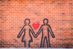 Koppla ihop förälskad besprutad målarfärg på väggen för röd tegelsten Royaltyfri Bild