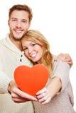 Koppla ihop förälskad hållande röd hjärta Arkivfoto