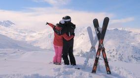 Koppla ihop förälskade ställningar på överkanten av det snöig berget och flyttningarna deras händer arkivfoto