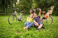 Koppla ihop förälskade tagande selfies med smartphonen i parkerar royaltyfria bilder
