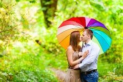 Koppla ihop förälskade ungdomarsom döljer från regnet under ett paraply Arkivbild