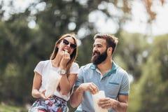 Koppla ihop förälskat ätapopcorn, och tycka om i ögonblick av lycka i staden parkera royaltyfri foto