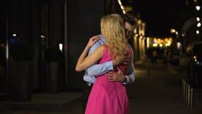 Koppla ihop förälskat affectionately och omfamna ömt under aftonmöte arkivfilmer