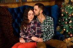 Koppla ihop förälskat bredvid en julgran som kramar och ser i väg från kameran in mot trädet royaltyfri fotografi
