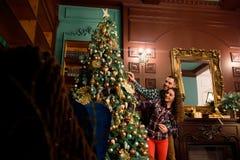 Koppla ihop förälskat bredvid en julgran som kramar och ser i väg från kameran in mot trädet royaltyfria bilder
