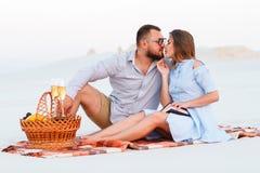 Koppla ihop förälskat dricka vin under romantisk matställe på stranden, de kyssande och hållande exponeringsglasen för barnpar i  Arkivfoto