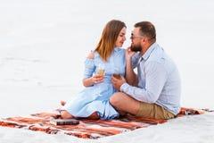 Koppla ihop förälskat dricka vin under romantisk matställe på stranden, de kyssande och hållande exponeringsglasen för barnpar i  Royaltyfri Foto