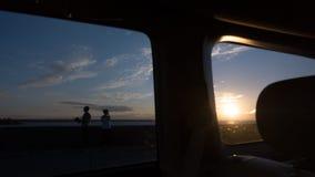Koppla ihop förälskat hålla ögonen på solnedgången på havet till och med sidan och det bakre fönstret av bilen Arkivbild