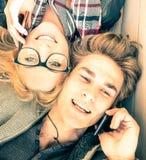 Koppla ihop förälskat ha gyckel med smartphones på vårtid Royaltyfri Bild