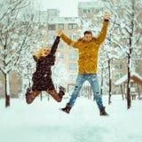 Koppla ihop förälskat ha gyckel och hoppa i snön Royaltyfri Bild