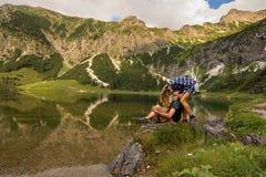 Koppla ihop förälskat kyssa framme av en bergsjö/par som framme kysser av härlig panorama med berg Arkivfoto