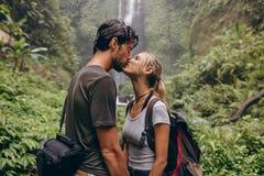 Koppla ihop förälskat kyssa nära en vattenfall i skog Royaltyfria Bilder