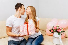 Koppla ihop förälskat, man ger en gåva, kvinna sitter hemma på soffan, begrepp av kvinnors dag royaltyfria foton