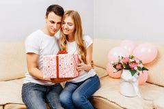 Koppla ihop förälskat, man ger en gåva, kvinna sitter hemma på soffan, begrepp av kvinnors dag royaltyfri foto