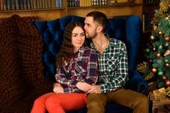 Koppla ihop förälskat nära en julgran som kramar och ser i väg från kameran in mot trädet arkivbild