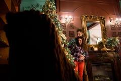Koppla ihop förälskat nära en julgran som kramar och ser i väg från kameran in mot trädet arkivfoto
