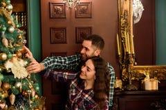 Koppla ihop förälskat nära en julgran som kramar och ser i väg från kameran in mot trädet arkivbilder